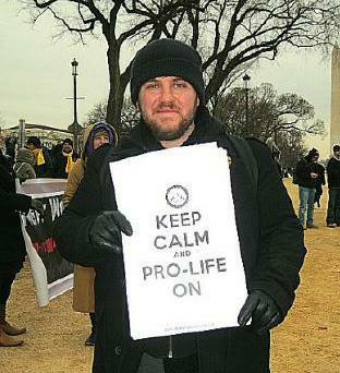 Smiling man at the March for Life holds sign that says, 'Keep Calm and Pro-Life On'