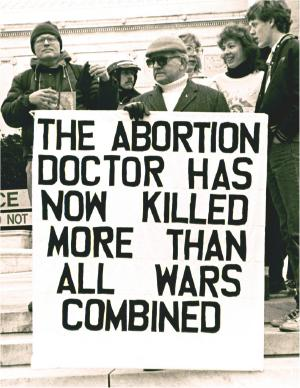 Man with sign: 'The Abortion Doctor Has Now Killed More than All  Wars Combined'