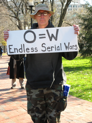 Man in combat fatigues holds sign that says 'O=W/Endless Serial Wars'