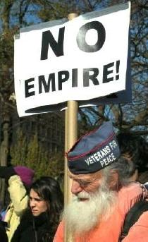 Old man with Veterans for Peace cap holds sign: 'No Empire!'