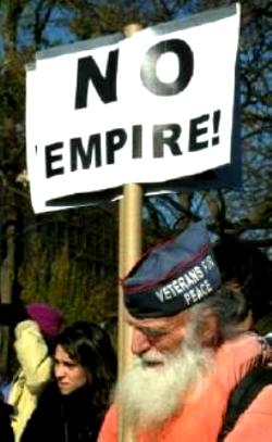White-bearded man wears 'Veterans for Peace' cap and carries sign that says, 'NO EMPIRE!'