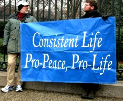 Two men hold white-on-blue 'Consistent Life' banner