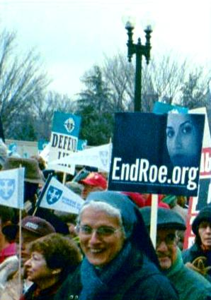 Marchers with 'EndRoe.org' and 'Defend Life' signs