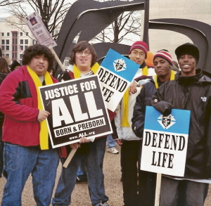 Five young men at March for Life with  'Defend Life' and 'Justice for All' signs