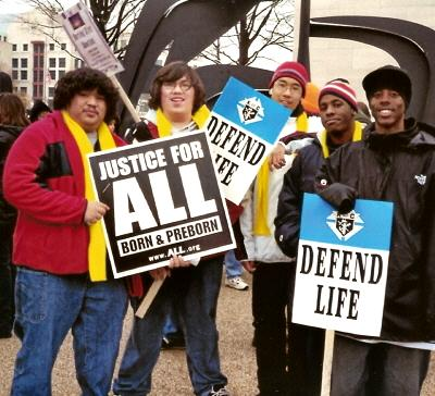Five young men at March for Life with signs: 'Justice for ALL' and 'Defend Life'