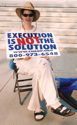 Young woman holds sign that proclaims, 'Execution is NOT the Solution'