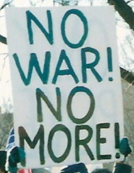 Large, hand-held sign that says: 'NO WAR! NO MORE!'