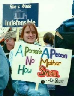 Woman with sign: 'A Person's a Person/No Matter How Small --Dr. Seuss'