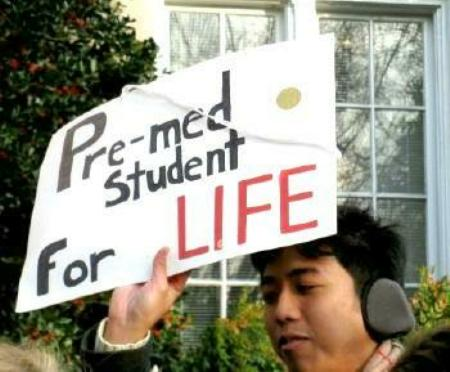 Young man holds sign: 'Pre-med Student For LIFE
