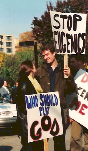 Young couple with signs: 'Stop Eugenics' and 'Who Should Play God'