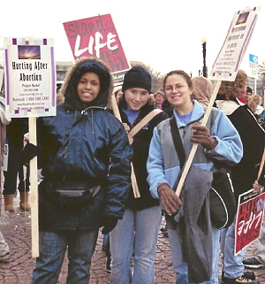 Three young women with pro-life signs