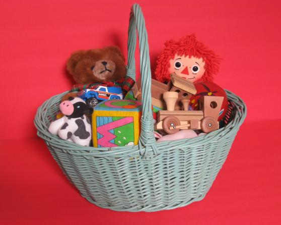 Basket of toys, including a miniature wooden train engine, a Teddy  Bear, and Raggedy Ann