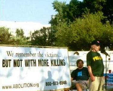 Activists with banner that says, 'We Remember the Victims...BUT NOT WITH MORE KILLING'