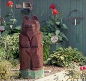 Mini-garden with large wooden bear